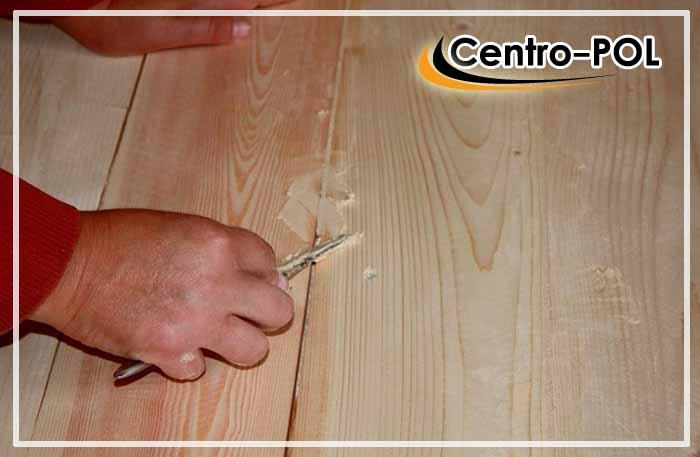 Нанесение клейстера на щели в деревянном полу